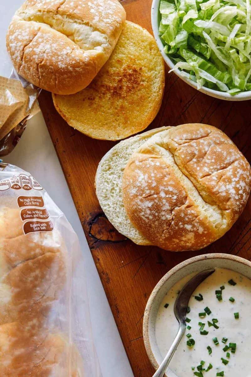 Ingredients for Nashville honey hot chicken sandwiches on a wooden cutting board.