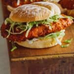 A close up of Nashville honey hot chicken sandwiches on a wooden cutting board.