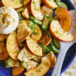 A close up of peach panzanella salad with a spoon.