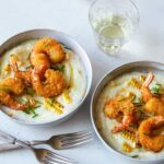 Bowls of fried shrimp and grits with forks and a drink.