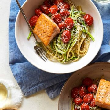 Seared salmon over 50/50 spaghetti with arugula and walnut pesto with a fork.