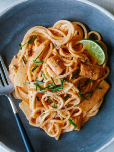 A close up of red curry noodles with a lime wedge and a fork.