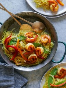 A pot of singapore noodles with shrimp and peppers and serving spoons.