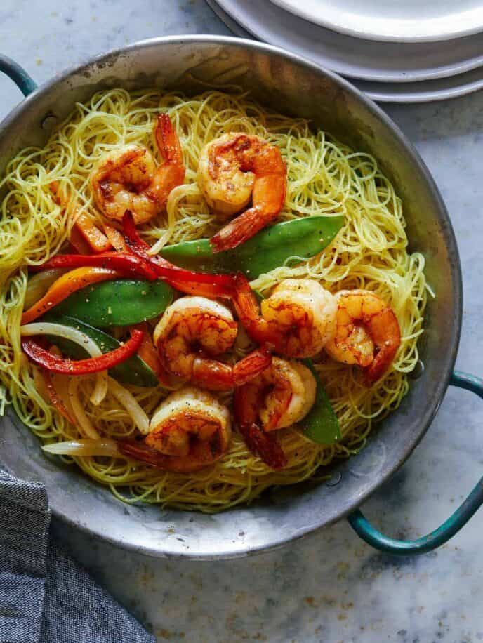 Singapore noodles in a big bowl with a stack of plates next to it.