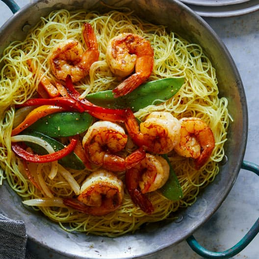 Singapore noodles in a big serving dish with plates on the side.