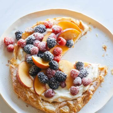 A summer fruit ricotta crostata with a slice removed.