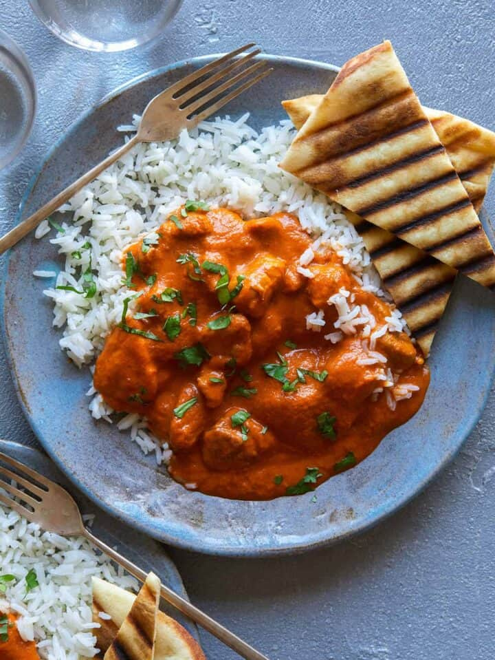 Indian butter chicken over rice with grilled naan and a fork.