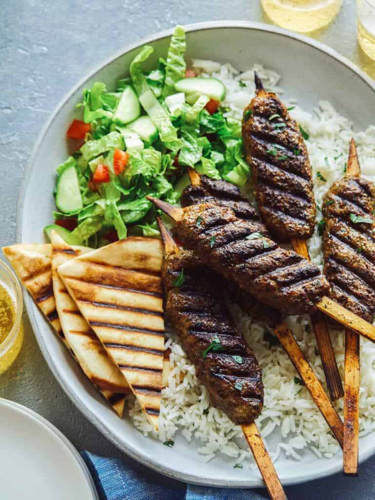 Lamb kofta on rice with pita triangles and salad.