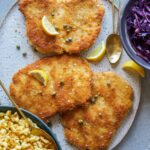 Schnitzel with buttered spaetzle with sweet and sour cabbage, lemon wedges and spoons.