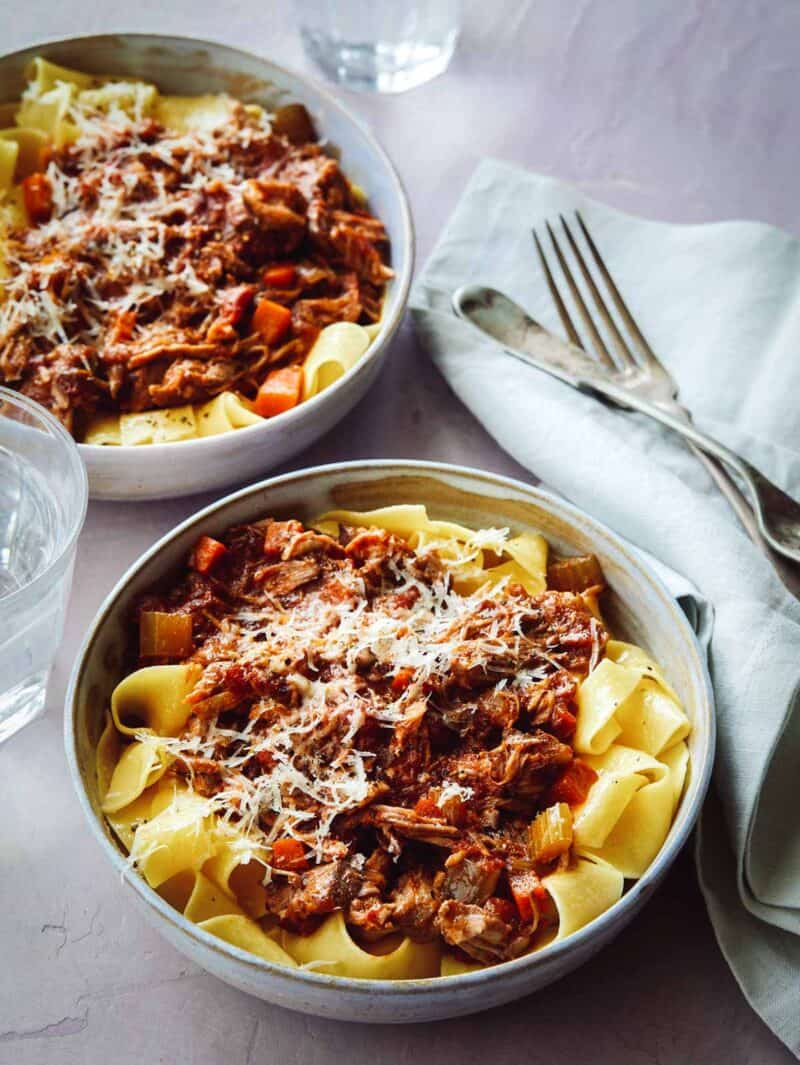 Pork Ragu on top of a bed of pappardelle noodles in two bowls.