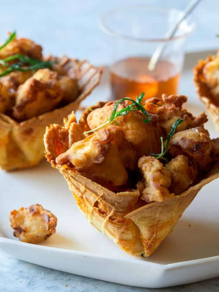A close up of popcorn chicken in cheesy waffle cups.