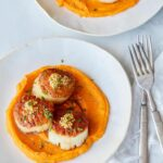 A plate of seared scallops over roasted sweet potato pureee with forks.