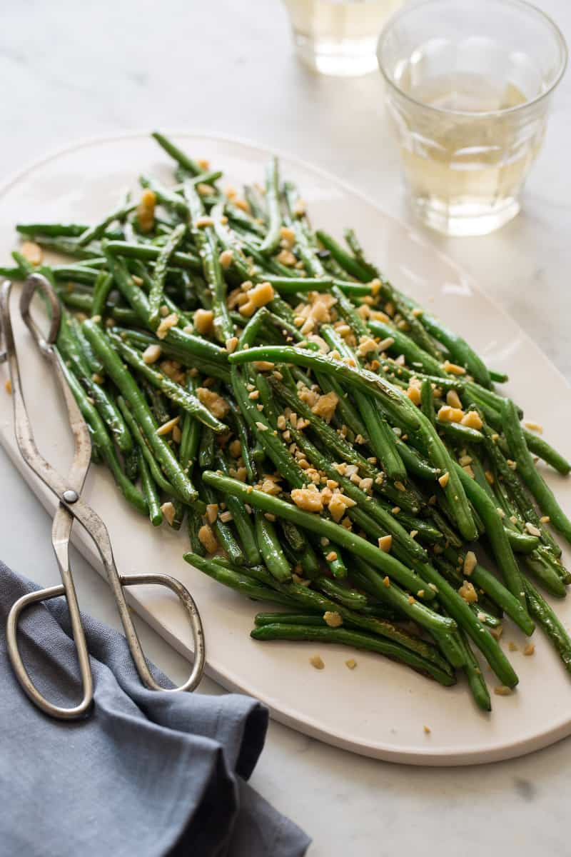 A platter of lightly roasted green beans with serving tongs.