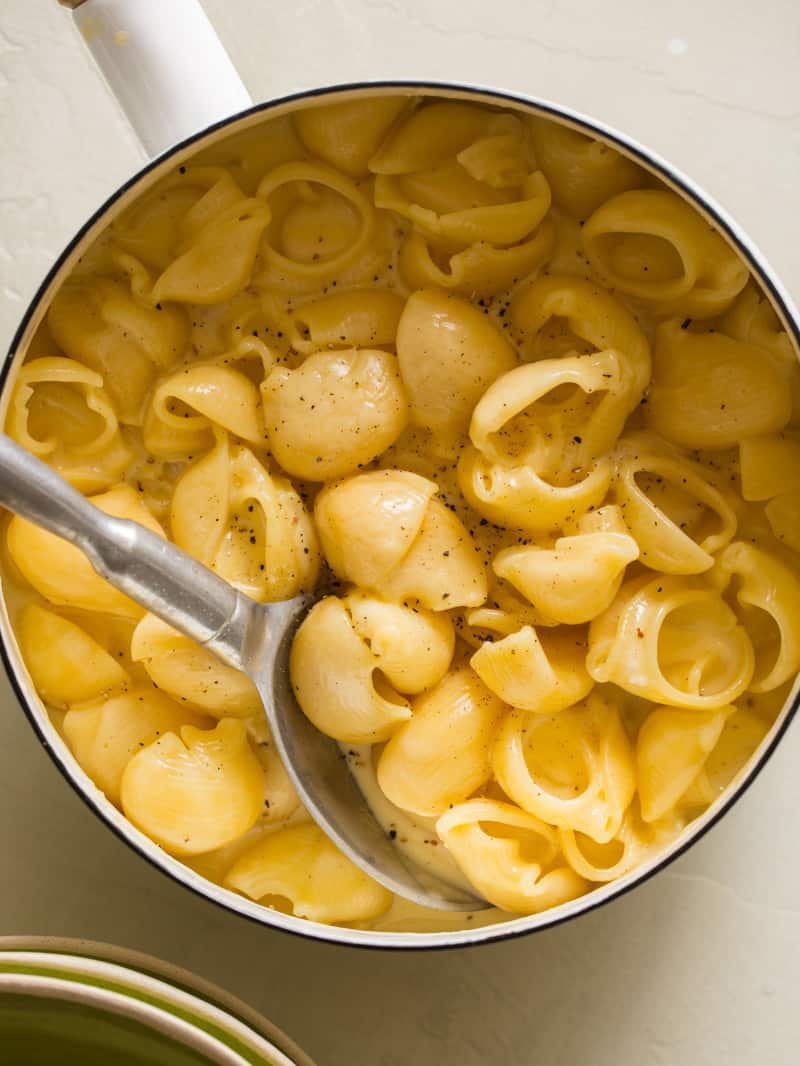 A close up of a pot of stovetop mac and cheese with a spoon.