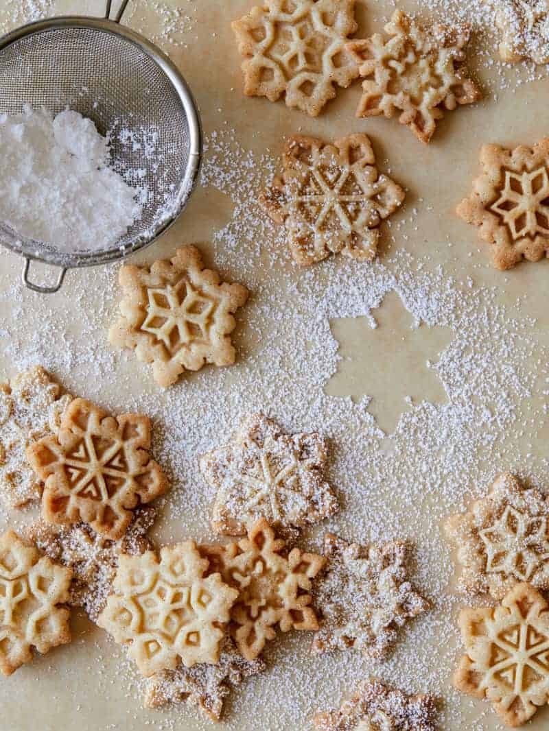 Gingerbread snowflake cookies being dusted with powdered sugar through a sieve.