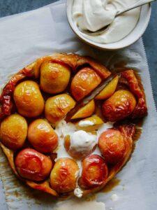 Sliced honey crisp apple tart tatin with melting whipped cream.