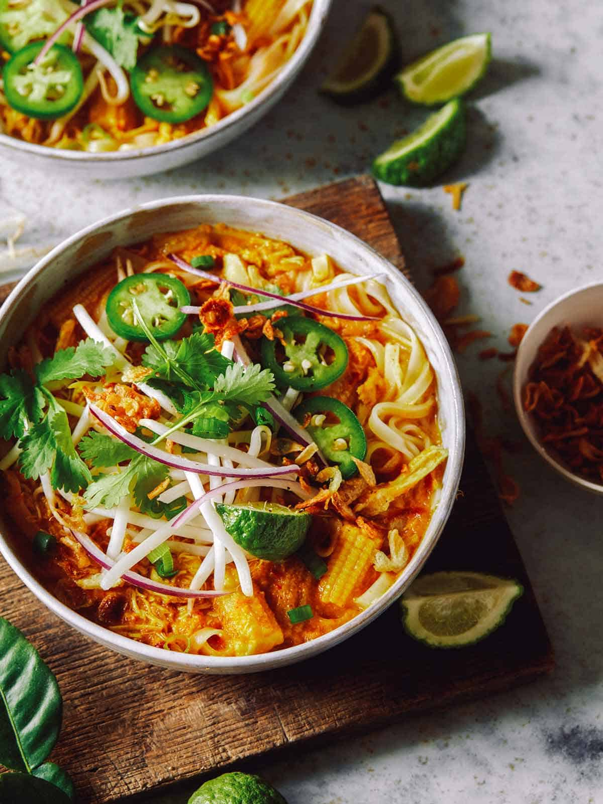Spicy chicken laksa in two bowls with onions on the side.