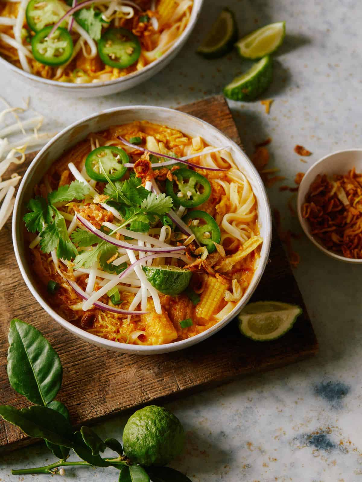 Spicy chicken laksa in a bowl garnished with jalapeños, red onion, and cilantro.