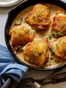 A close up of crispy chicken thighs with a creamy mushroom sauce in a skillet.
