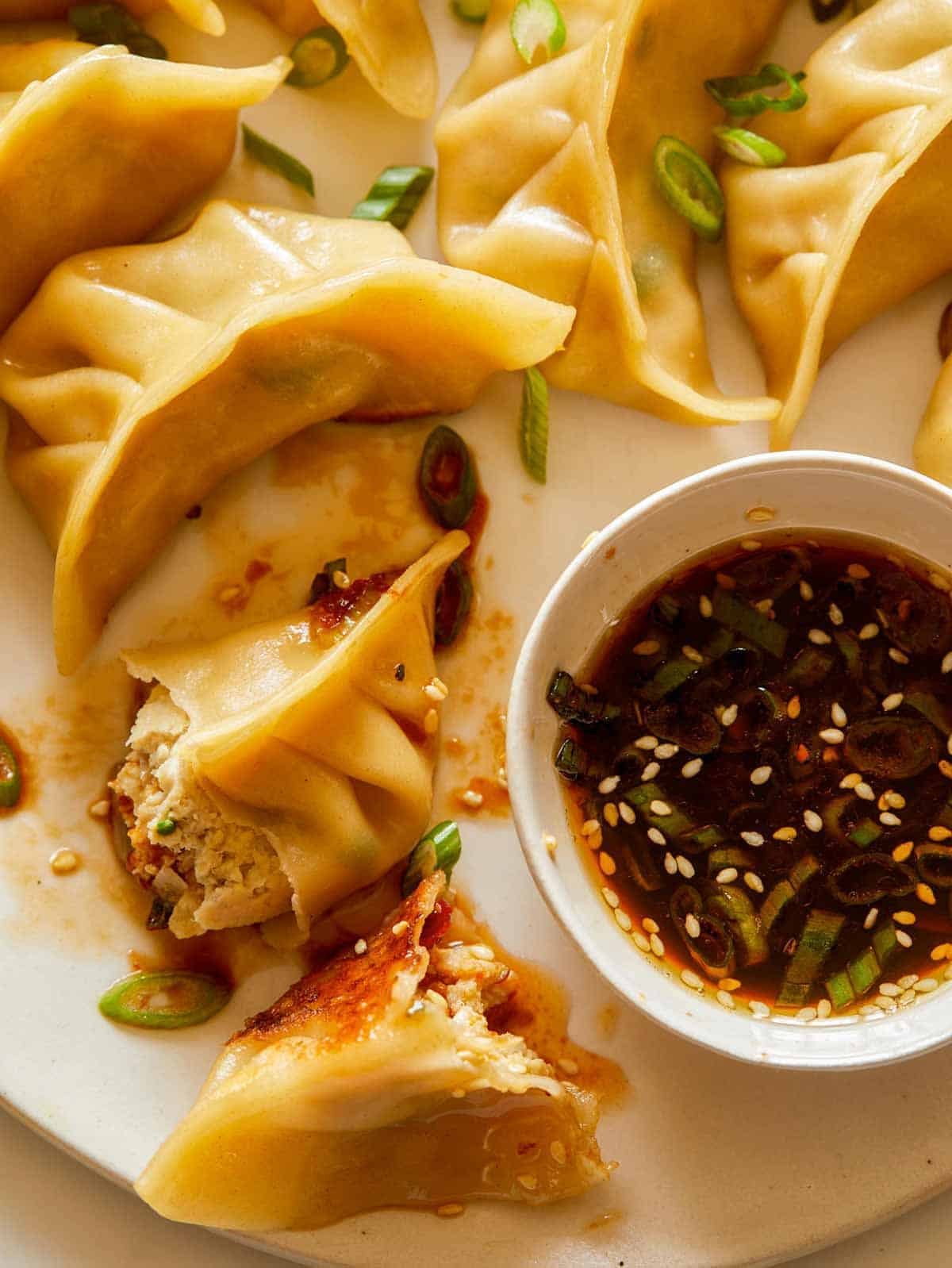 A close up of ginger chicken pot stickers with green onions and sauce.