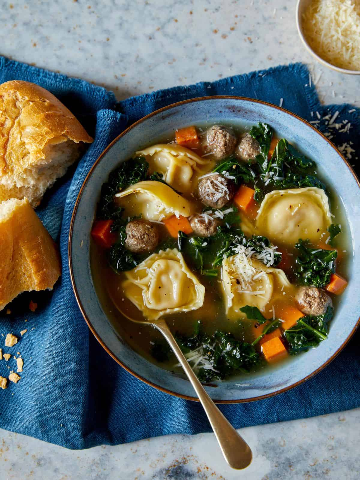 Tortellini, turkey sausage, sweet potato, and kale soup with a spoon and bread.