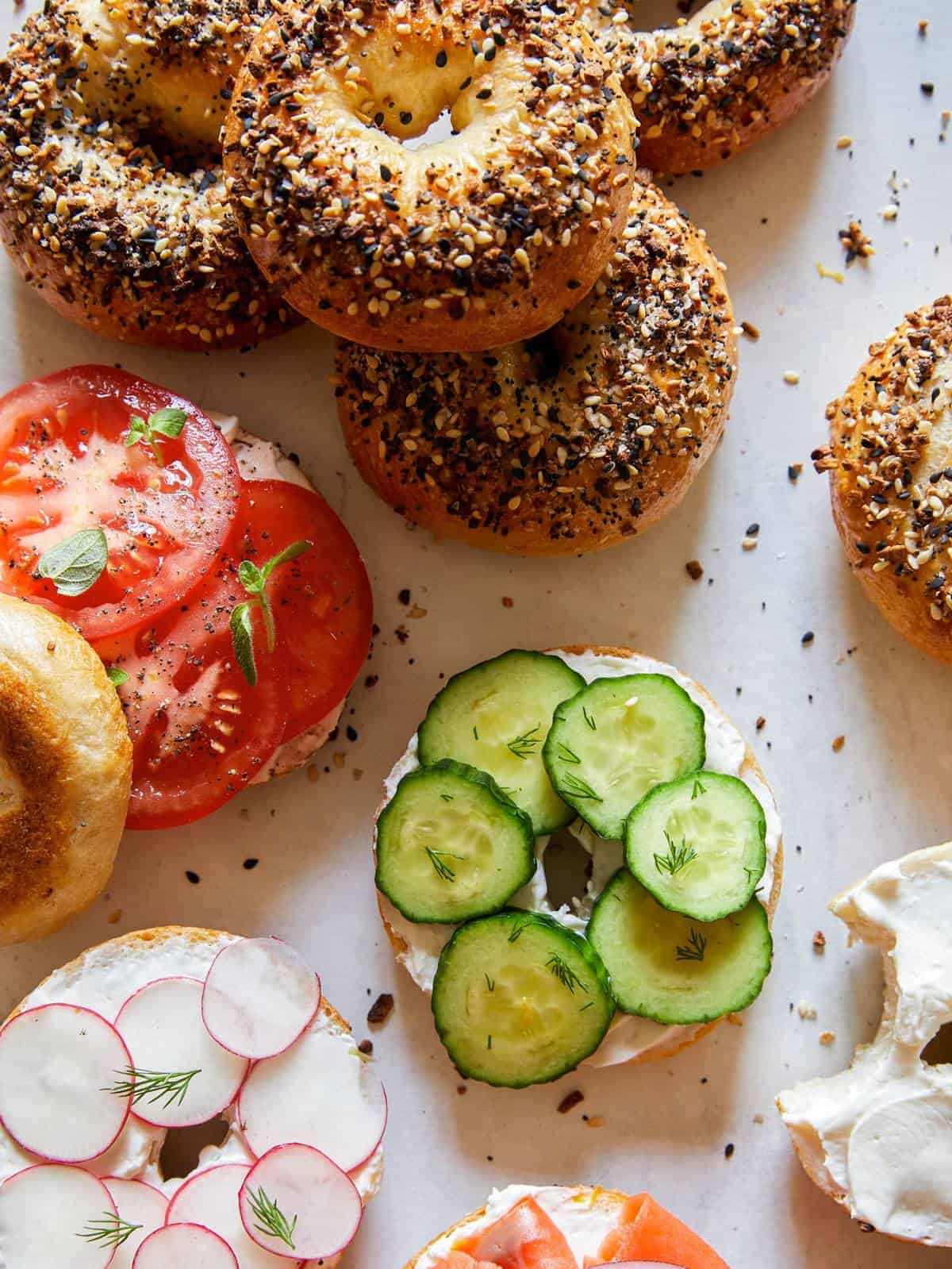 Everything bagels, some sliced and topped with cream cheese and veggies.