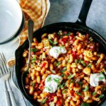 Taco pasta in a skillet with a spoon and forks.