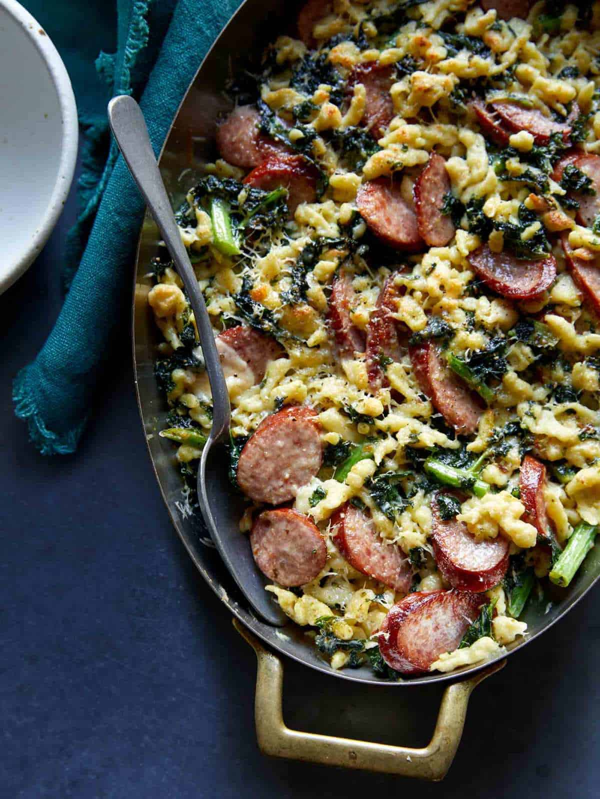 A close up of sausage kale and spaetzle pesto bake in a pan with a spoon.