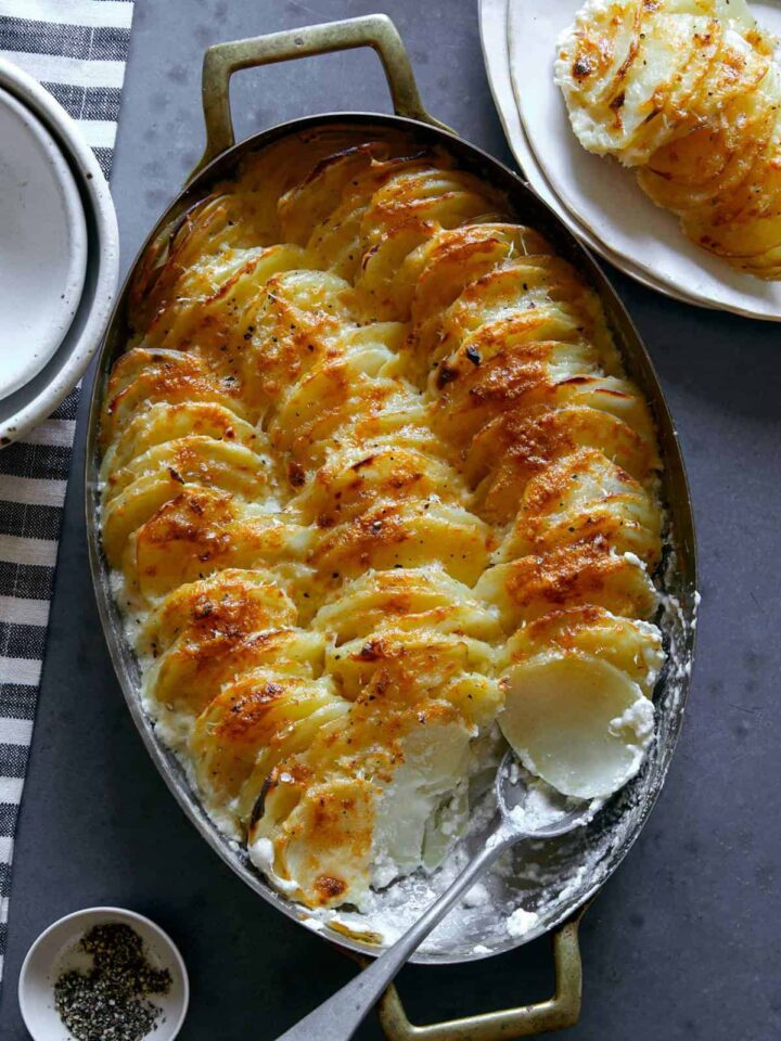 Cheesy garlic potato gratin in an oval baking dish with a scoop taken out with a spoon.