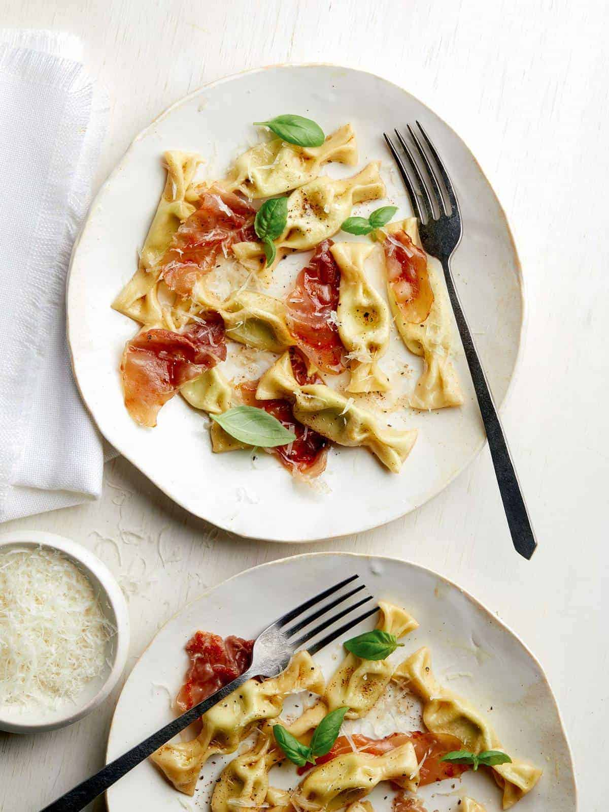 Plates of sweet pea caramelle with prosciutto and forks.