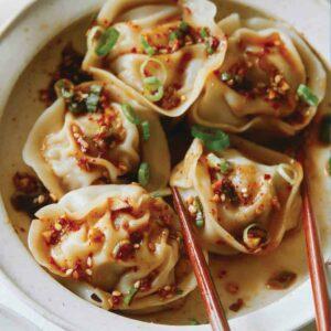 A close up of pork and shrimp dumplings with chopsticks.