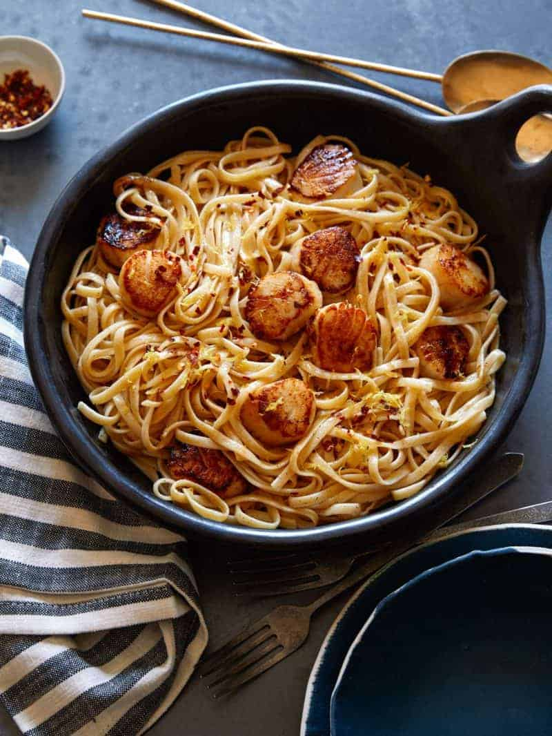 Linguine with brown butter sauce and scallops in a skillet.