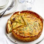 A sliced spring quiche with hash brown crust.