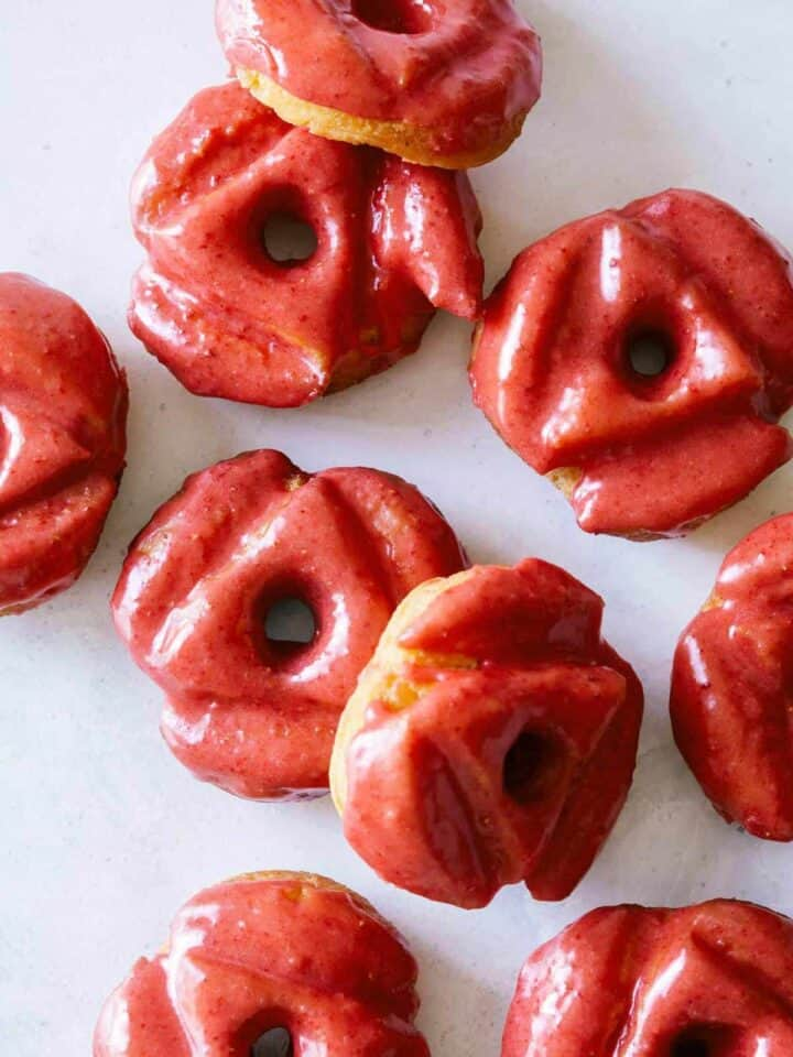 A close up of strawberry glazed old fashioned doughnuts.