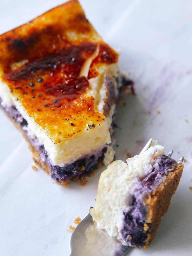 A close up on a Blueberry Cheesecake Crème Brûlée bar with a chunk taken out by a fork.