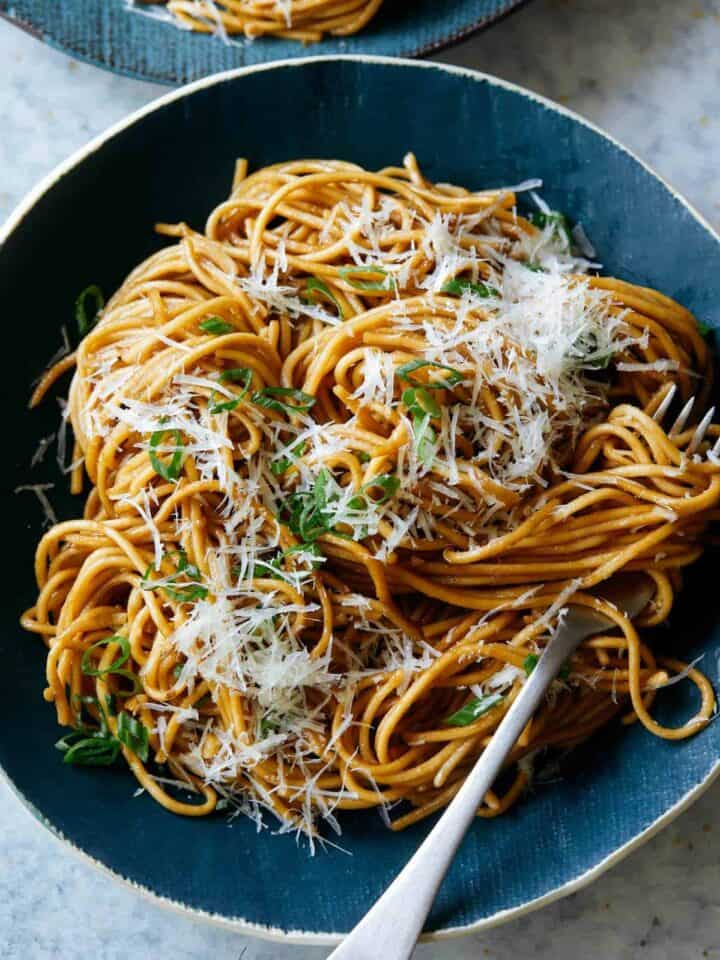 Garlic noodles garnished with cheese on a blue plate with a fork.