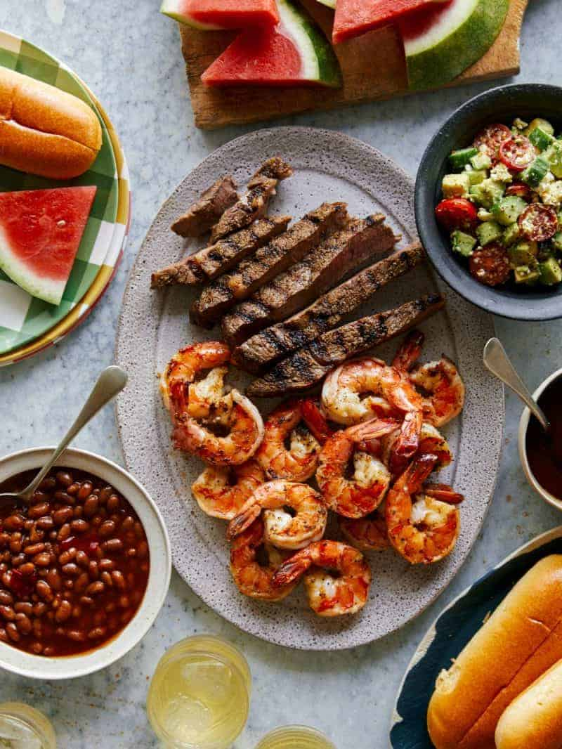 Grilled shrimp and steak platter with sides of salad, beans, and watermelon.
