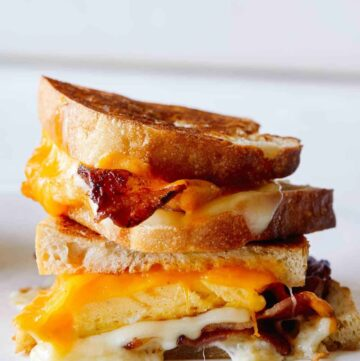 A close up of stacked extra cheesy breakfast grilled cheese sandwiches.