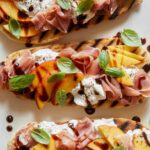 A close up of grilled flatbreads topped with peach, prosciutto, and burrata.
