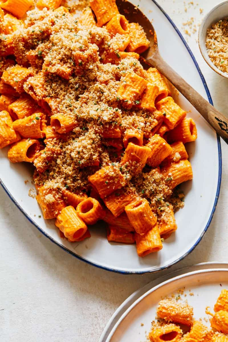 A platter of romesco rigatoni sauce with some served on a plate next to the platter.