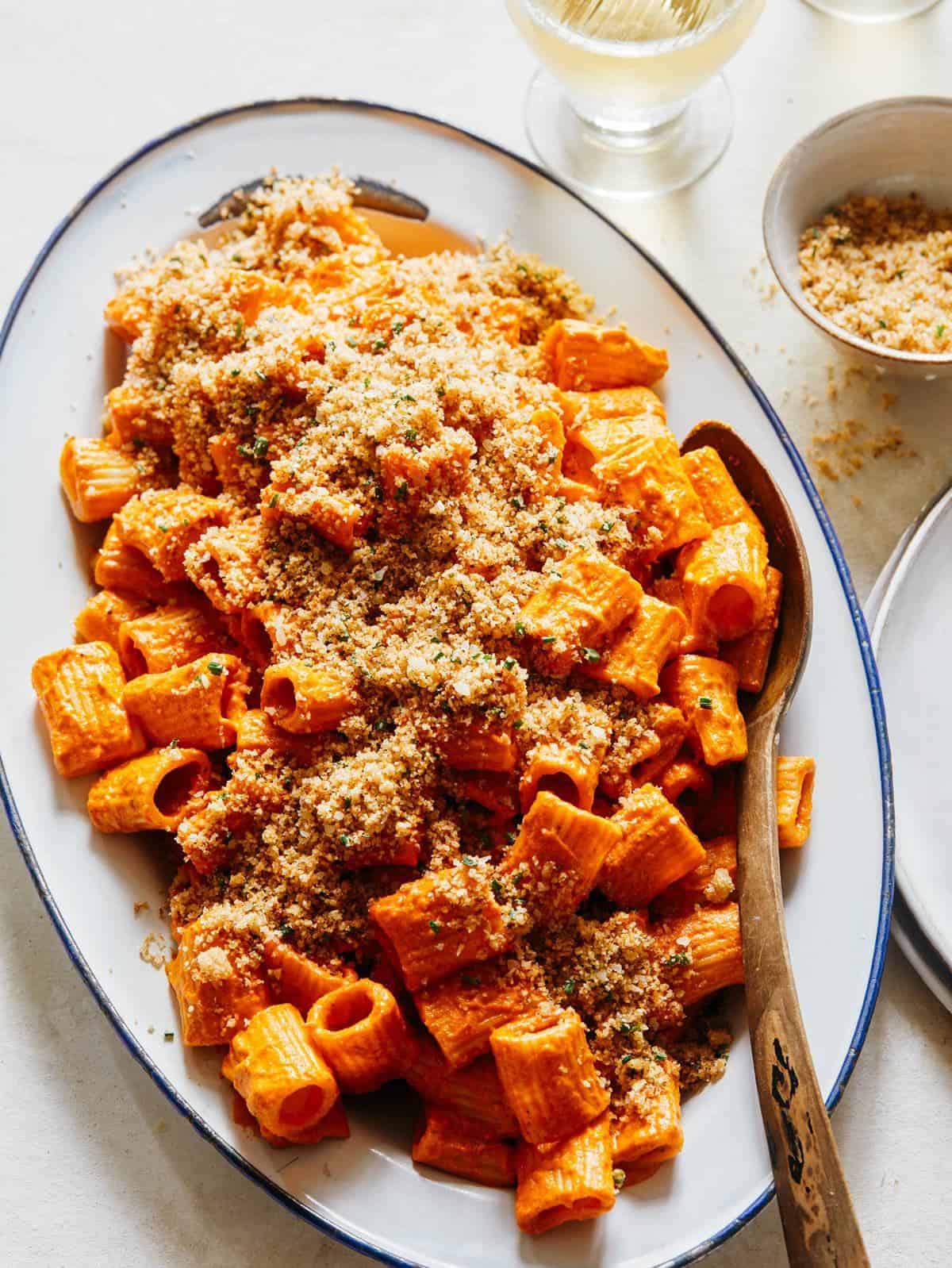 Romesco sauce rigatoni topped with breadcrumbs on a platter with a spoon.