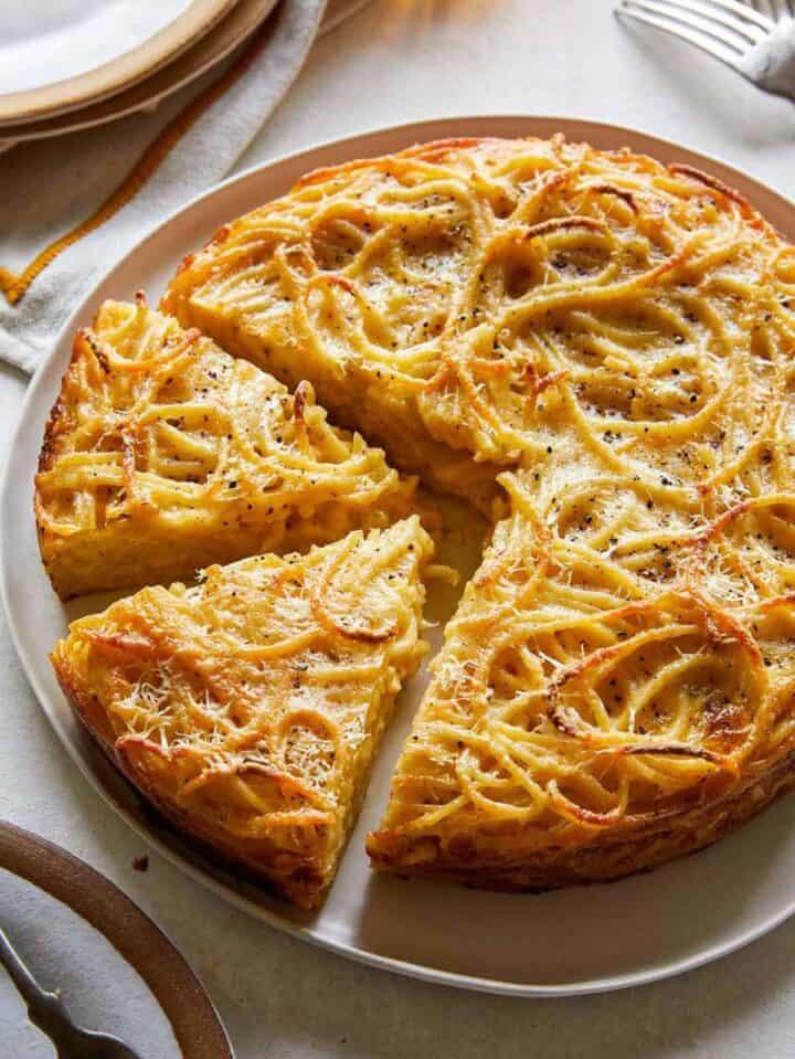 Cacio e pepe pasta pie with slices cut, a dinner recipe.