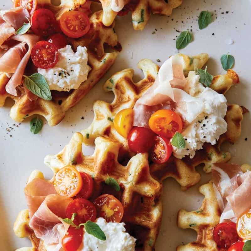 Cheesy herb waffles topped with prosciutto, burrata and tomatoes.e