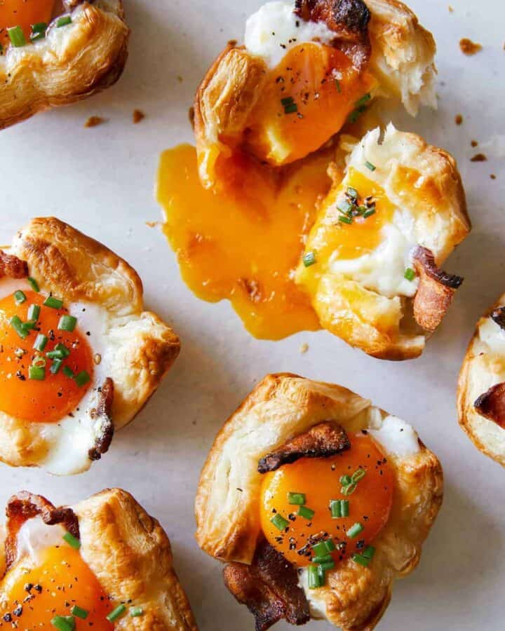 A close up of cheesy flaky breakfast cups with broken yolk.