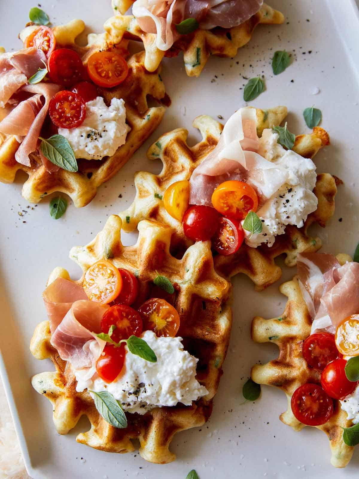Cheesy herb waffles topped with prosciutto, burrata and tomatoes.