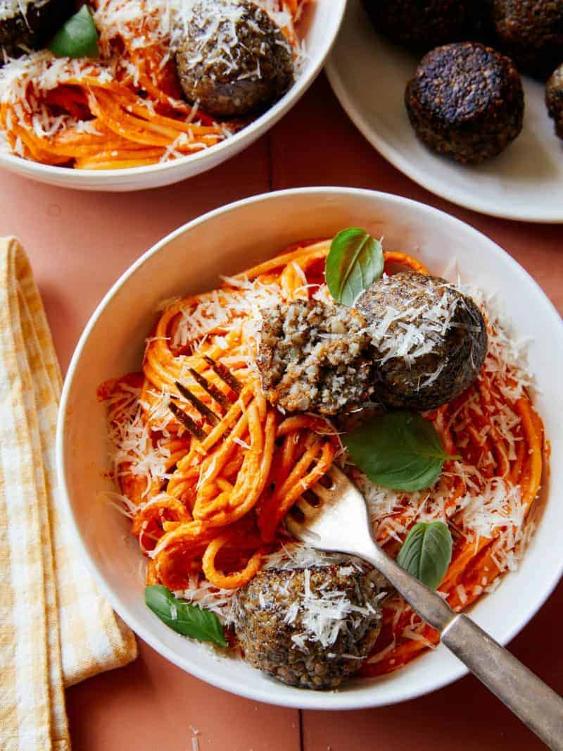 Vegan creamy roasted red pepper spaghetti and meatballs in a bowl with a fork.