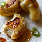 A close up of crispy chicken potstickers with green onions and sauce.