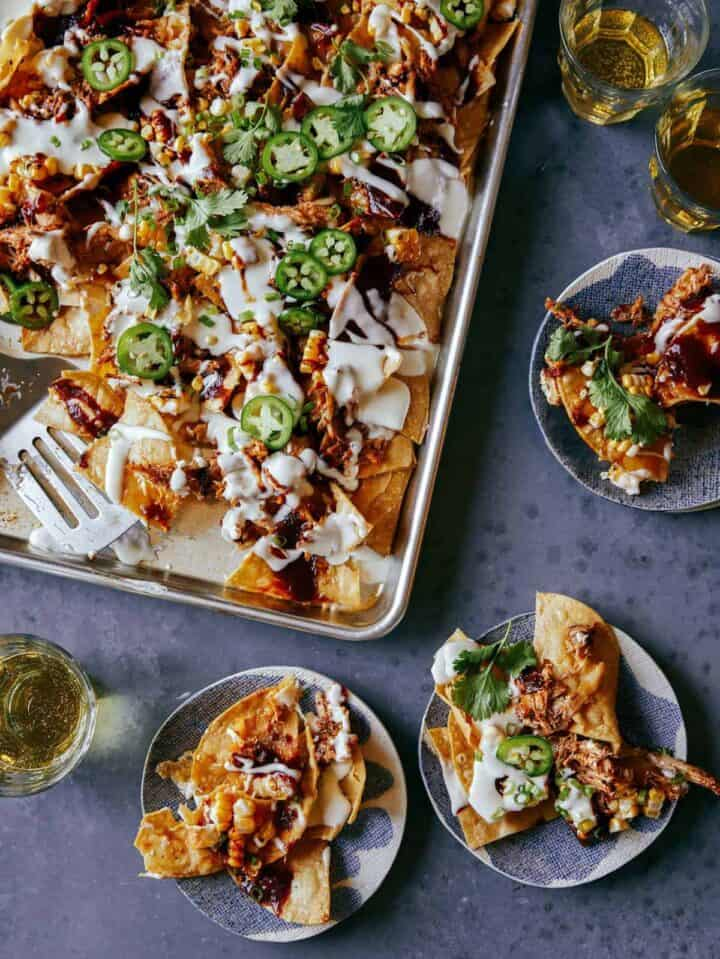 A sheet pan of chipotle chicken nachos with servings on small plates, a chicken dinner idea.
