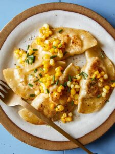 Creamy shrimp and corn ravioli on a plate with a fork.
