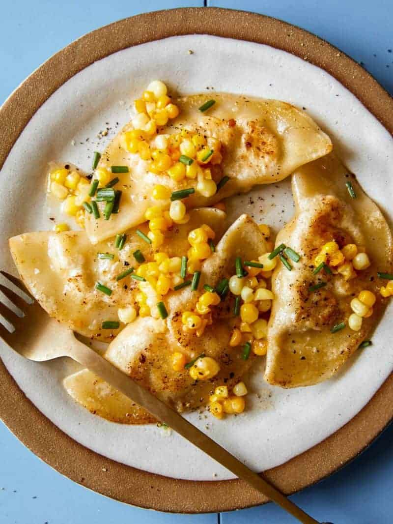 Shrimp and corn ravioli on a plate and a fork.